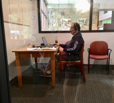 man using a laptop and headphones in study room