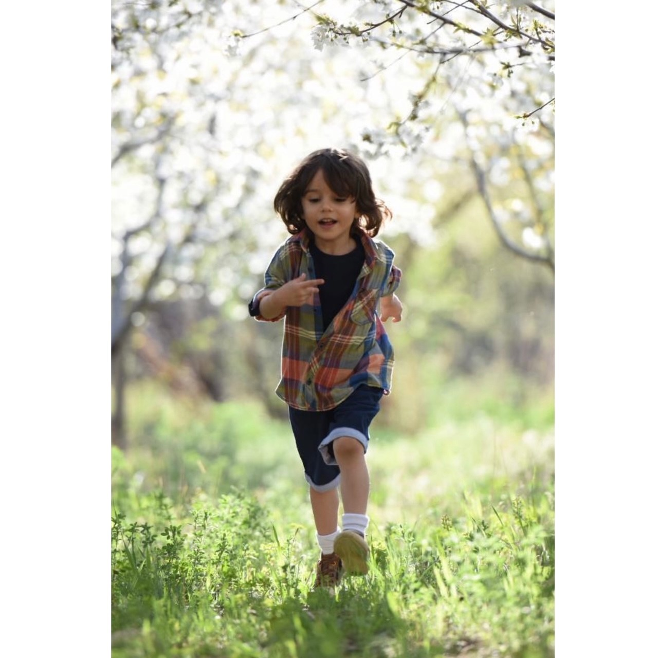 child in meadow running towards viewer